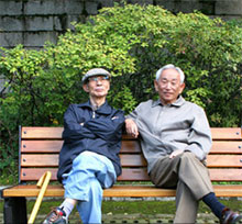 IKOR two Asian seniors sitting on bench